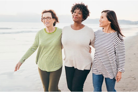 Three retired women walking on the beach