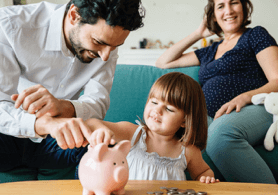A couple with their daughter playing with a piggybank