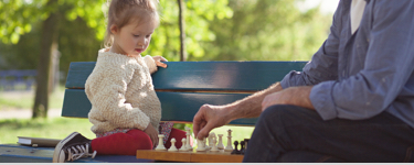 Man playing chess on a park bench with his granddaughter