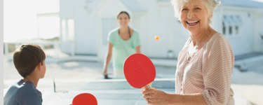 Boy playing ping pong with his mother and grandmother