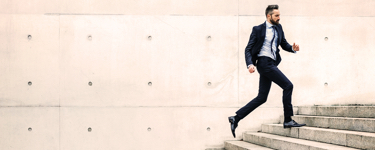 Young man in a suit running up a flight of stairs