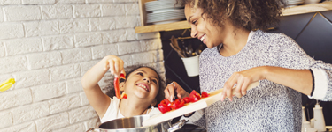 Mother laughing with her young daughter while cooking