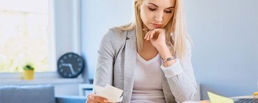 Woman is thinking while looking at her bills