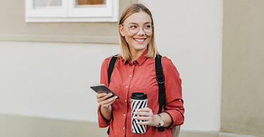 Photo of a young woman smiling and looking into the distance while holding a coffee to-go and mobile phone.