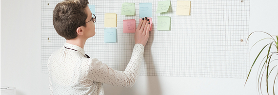 Professional woman placing sticky notes on a board