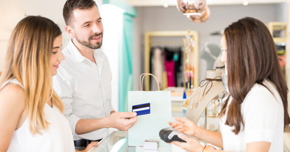 Young couple in a shop pays with a credit card