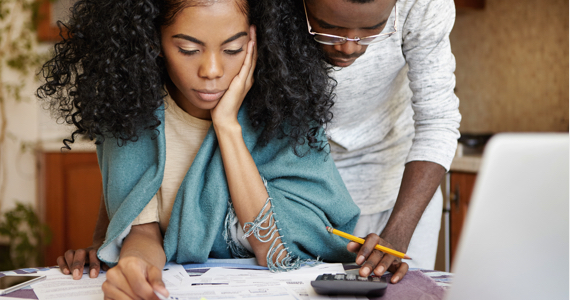 Young man and young woman do their accounting with a calculator