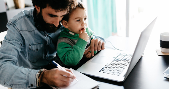 Man writing in notebook with child looking at laptop