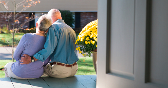 Retired couple hugging on the front porch of their house
