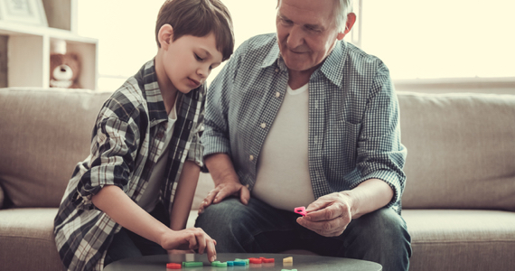 Little boy playing a game with his grandfather
