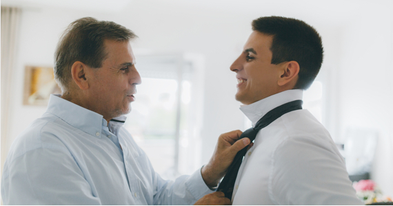 Man knots the tie of a younger man