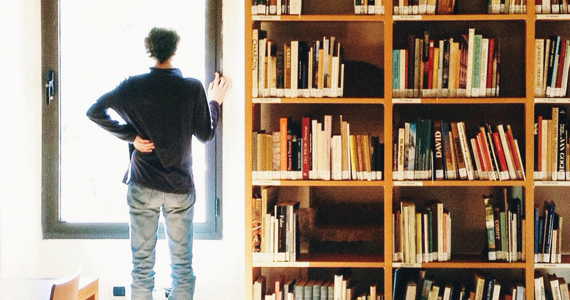 Man looks out window next to bookcase
