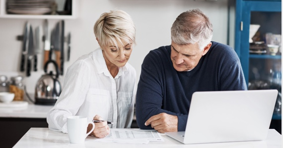 Couple looks at a document on a kitchen counter
