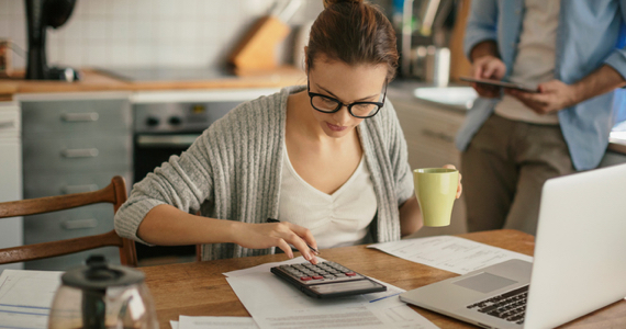 Young woman sitting at her kitchen table doing her accounts with her calculator