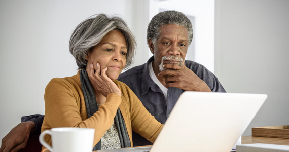 Retired couple deep in thought looking at a laptop