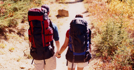 Woman and man with backpacks walk on a path while holding hands