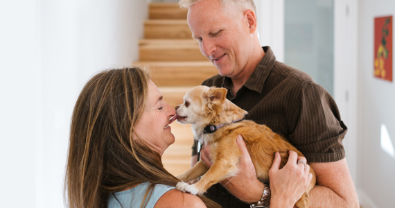 Retired couple holding a small dog