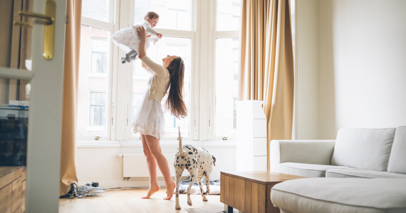 Happy woman raises her baby in the air in her living room
