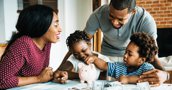 Parents with their two kids smiling and playing with a piggybank.