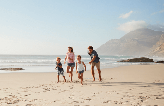 Parents with their children running on a beautiful beach