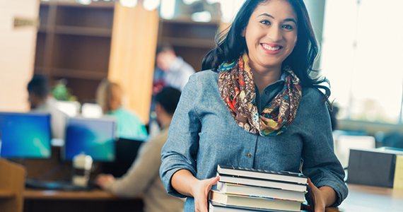 Female student in a library smiles while holding books in her hands
