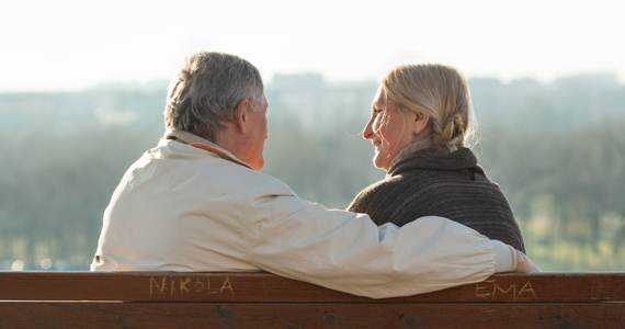 Retired couple on a park bench smile at each other
