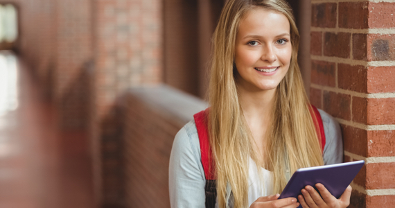 Young female student in a college hallway is holding a tablet while smiling