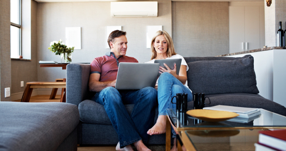 Woman shows her tablet to her spouse on a couch