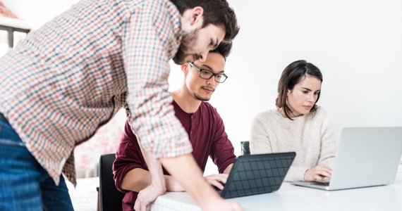Three people working together while looking at their computers