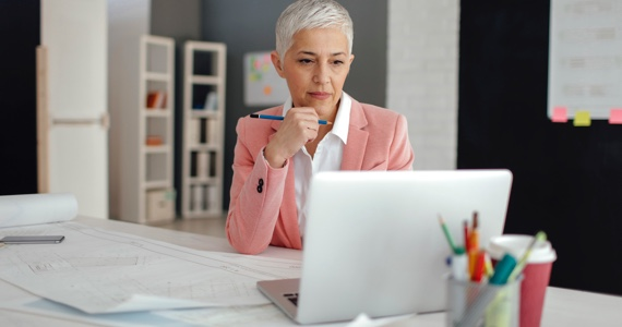 White haired woman at her desk is looking at her computer