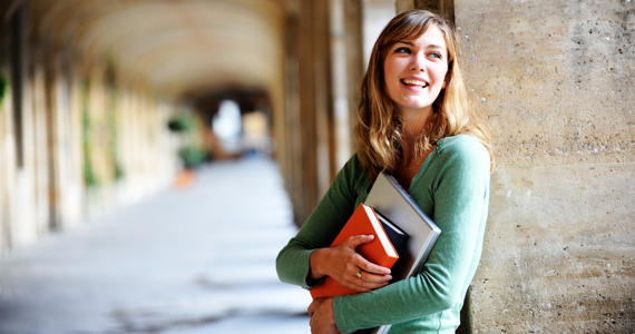 Young woman on university campus smiles while holding her books in her arms