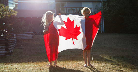 Two children holding a Canadian flag