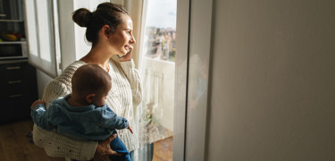 Woman holding baby and speaking on the phone while looking out the window