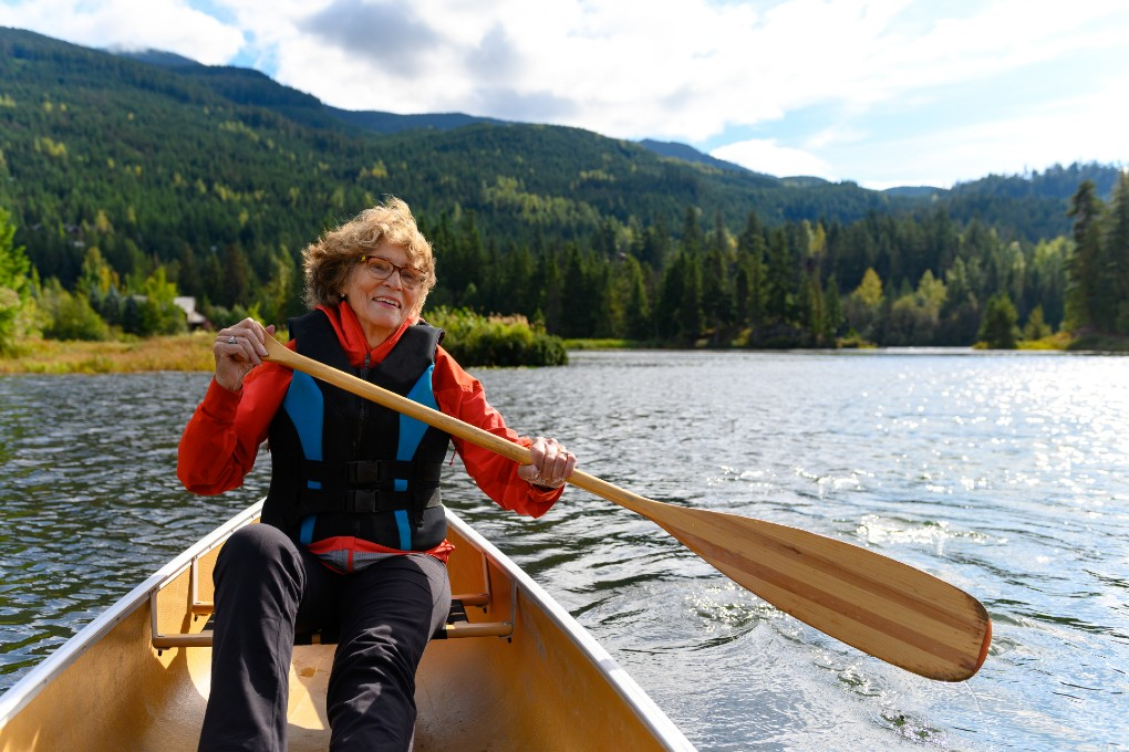 Retired woman paddling a canoe