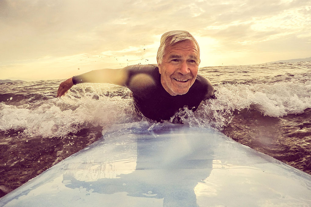 Retired man smiling on a surfboard