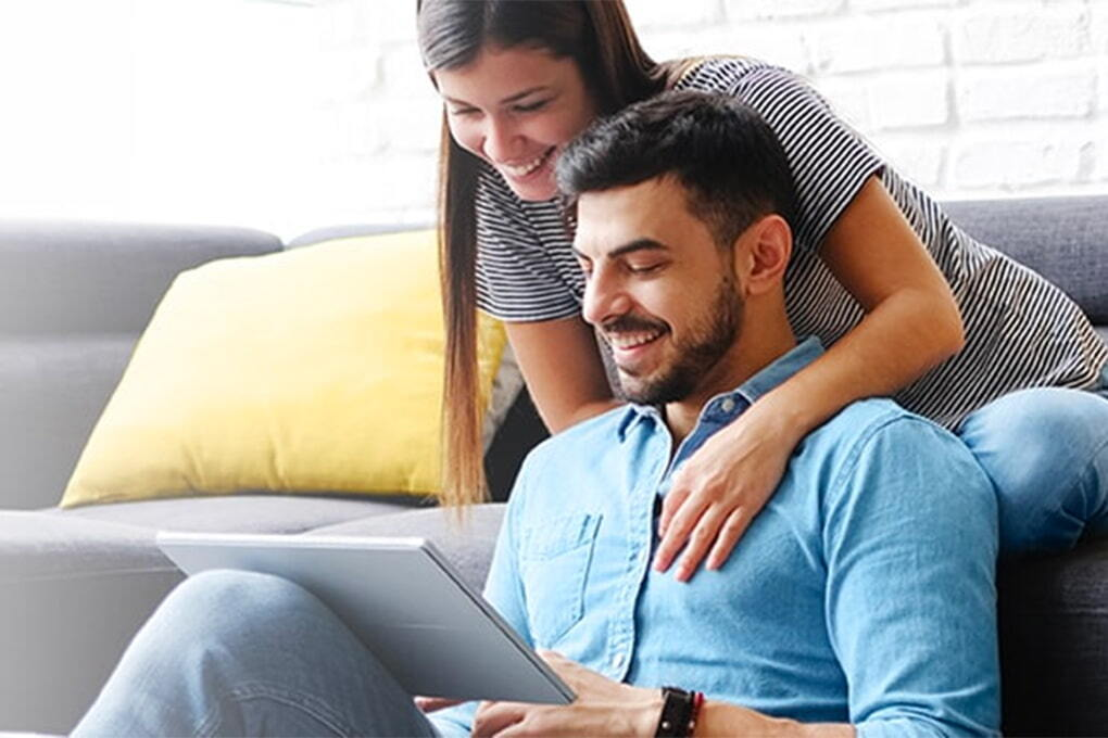 Photo of an happy couple sitting on a sofa and looking at a tablet