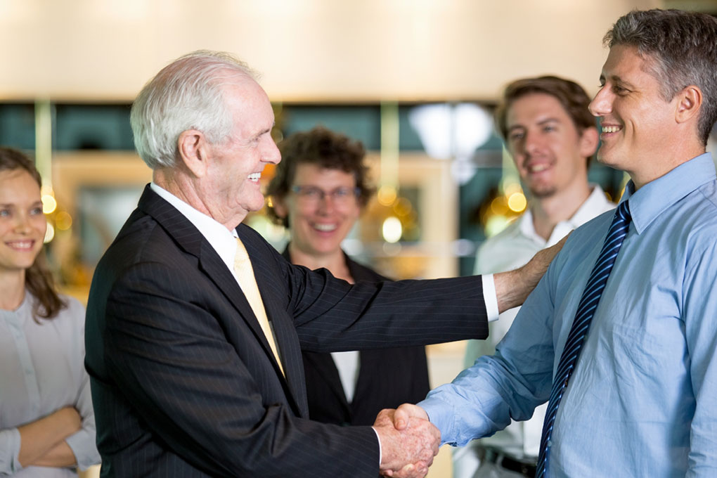 Smiling Business Leader Congratulating Colleague